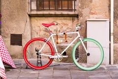 Een fiets met de binnen kleuren van de Italiaanse vlag naast een muur stock foto's