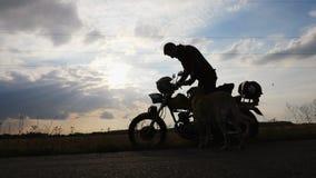 Een fietser met een hond gaat zitten op een motorfiets stock videobeelden