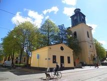 Een fietser met een lopende hond en een gele kerk royalty-vrije stock afbeeldingen