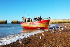 Een fijne rode en gouden Hastings-visserijtreiler komt aan wal in rots-a-Nore, Hastings, Oost-Sussex, Engeland royalty-vrije stock fotografie