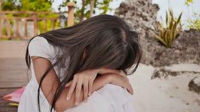 Een Filippijns schoolmeisjemeisje met een rugzak zit en schreeuwt dichtbij de tropische kust Droevige stemming stock video