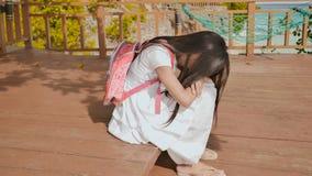Een Filippijns schoolmeisjemeisje met een rugzak zit en schreeuwt dichtbij de tropische kust Droevige stemming stock foto's