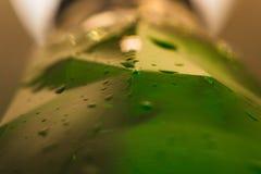 Een fles bier en het water laten vallen dichte omhooggaand royalty-vrije stock afbeelding