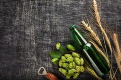 Een fles bier met groene hop, aartjes en opener op een zwart gekrast schoolbord royalty-vrije stock afbeeldingen