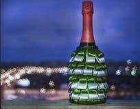 Een fles champagne met linten dat van groen wordt verfraaid en wit stock afbeeldingen