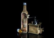 Een fles door berkeschors, een koffiemolen en een gouden metaal g wordt behandeld dat Stock Foto