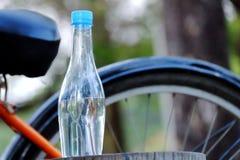 Een fles drinkwater op een oud hout bij het park met vertroebelde een fietsparkeren op de benedenverdieping stock foto