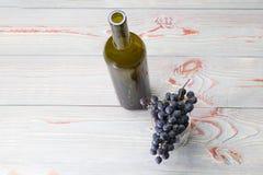 Een fles en een glas daarin zijn een tak van donkere druiven, tegen een grijze achtergrond in een houten achtergrond stock foto