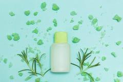 Een fles etherische olie en zout met verse kruidrozemarijn op een blauwe achtergrond Hoogste mening stock foto's
