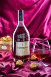 Een fles Franse cognac Hennessy V S O P met een glas cognac en chocolade royalty-vrije stock foto's