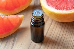 Een fles grapefruitetherische olie met verse roze grapefruit stock fotografie
