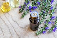 Een fles hyssopetherische olie met het verse bloeien hyssop stock foto