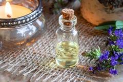 Een fles hyssopetherische olie met het verse bloeien hyssop stock afbeeldingen