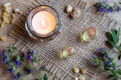 Een fles hyssopetherische olie met het verse bloeien hyssop stock fotografie