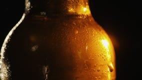 Een fles koud bier op een zwarte achtergrond Een straal van licht verlicht het prachtig royalty-vrije stock afbeelding