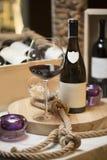 Een fles rode wijn en een glas wijn op een houten die plaque, met kaarsen in purpere kandelaars en dik wordt verfraaid Stock Foto