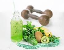 Een fles van komkommer smoothies, fruit en het meten van band op een witte lijst Stock Afbeelding