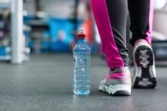 Een fles water dichtbij de voeten van het meisje Royalty-vrije Stock Fotografie