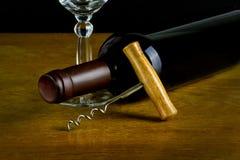 Een fles wijn aan de kant met een glas en een kurketrekker Stock Fotografie