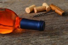 Een fles Witte Zinfandel wijn met kurketrekker en kurkt op een rustieke houten lijst stock afbeeldingen