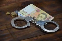Een foto van een bepaalde hoeveelheid Oekraïense geld en politiehandcuffs Concept onwettige inkomens van Oekraïense burger stock fotografie
