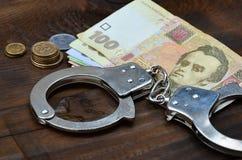 Een foto van een bepaalde hoeveelheid Oekraïense geld en politiehandcuffs Concept onwettige inkomens van Oekraïense burger royalty-vrije stock foto's