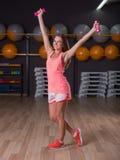 Een foto van gemiddelde lengte van een glimlachend jong meisje met roze domoren op een gymnastiekachtergrond Een sportief meisje  Royalty-vrije Stock Afbeelding