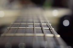 Een foto van een gitaarhals met koorden en een houten textuur - het materiaal van een gitaarhals Selectieve nadruk op één gitaard stock afbeelding