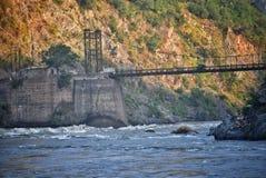 Een foto van een ijzer en een houten brug over een rivier met berg bij achtergrond die door zonnestralen vroeg in de ochtend rake royalty-vrije stock foto's