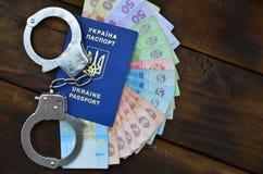 Een foto van een Oekraïens buitenlands paspoort, een bepaalde hoeveelheid Oekraïens geld en politiehandcuffs Het concept het arre stock fotografie