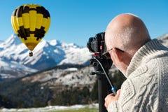 Een fotograaf bovenop de berg met hete luchtballon Royalty-vrije Stock Afbeelding
