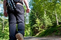 Een fotograaf die in het bos wandelt Stock Foto