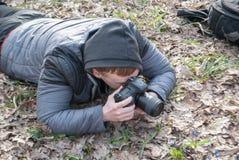 Een fotograaf, een mannelijke foto met een camera, fotografeert een macro van een bloem royalty-vrije stock afbeelding