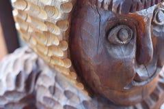 Een fragment van een oud houten beschadigd standbeeld tegen de tijd dat en aard stock fotografie