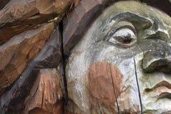 Een fragment van een oud houten beschadigd standbeeld tegen de tijd dat en aard royalty-vrije stock fotografie