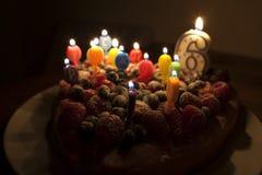 Een fruitcake met kaarsen voor een zesde verjaardag Stock Fotografie