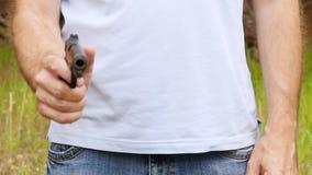 Een gangster in het hout neemt een zwart kanon en richt het op de camera, langzaam close-up stock videobeelden