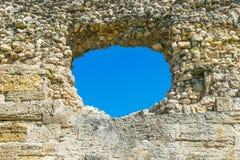 Een gat in de steenmuur en de blauwe hemel op de achtergrond, een geru?neerde muur met een gat stock foto