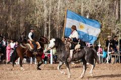 Een Gaucho met Argentijnse vlag die een paard in e berijdt Stock Afbeeldingen