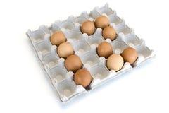 Een geïsoleerd close-up van bruine kippeneieren lag in een kartondienblad in de vorm van aantal 12 Het Concept van Pasen royalty-vrije stock foto's