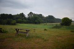 Een geïsoleerde houten bank in platteland Vogelverschrikkers, omheining, bos, gebied op de achtergrond stock afbeeldingen