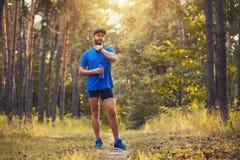 Een gebaarde die atleet treft voor een ochtend voorbereidingen langs een schilderachtige bosweg in werking wordt gesteld stock afbeeldingen