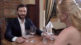 Een gebaarde mens in een kostuum neemt een blondemeisje door de hand Het paar zit bij een lijst in een modieus restaurant stock video