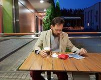 Een gebaarde mens op middelbare leeftijd van Kaukasische verschijning zit bij een lijst in een de zomerkoffie in de avond, letten stock fotografie