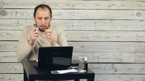 Een gebaarde mens werkt bij de computer en de hoest stock video