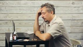 Een gebaarde mens werkt bij de computer en de hoest stock footage