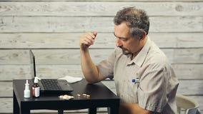 Een gebaarde mens werkt bij de computer en de hoest stock videobeelden