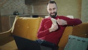 Een gebaarde mens werkt thuis met laptop, houdend een groot pakje van contant geld Een volwassen mens glimlacht Hij is gelukkig stock footage