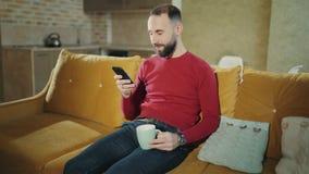 Een gebaarde mens zit thuis met mobiele telefoon en surft in sociale netwerken om te communiceren, flirten Ochtend E stock video
