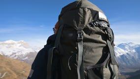 Een gebaarde mens in zonnebrilhoed met een rugzak en een camera bevindt zich hoog in de bergen en kijkt op de zijlijn stock video